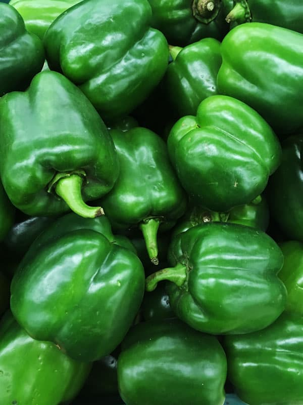 close up of a basket of green bell peppers