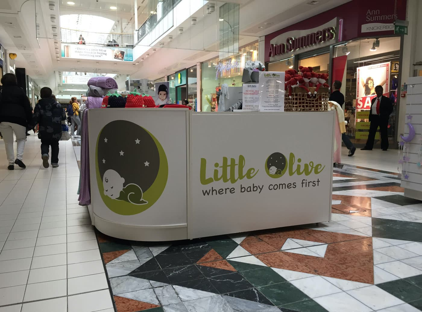 a shopping centre with a stall by Little Olive, logo and signage designed by Bell Pepper Design